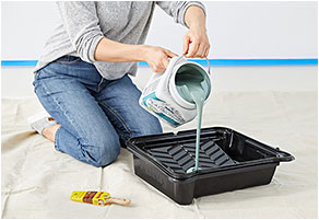 Woman filling roller tray with paint