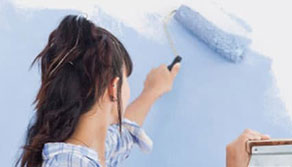 Woman rolling paint onto a wall