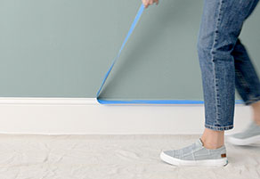 Woman removing painter's tape from baseboard